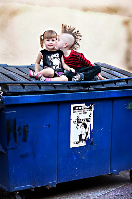 Child with Mohawk kisses sister's cheek while sitting on a dumpster in an urban location
