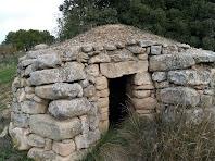 Detall de la part frontal de la barraca amb paravents per protegir l'entrada