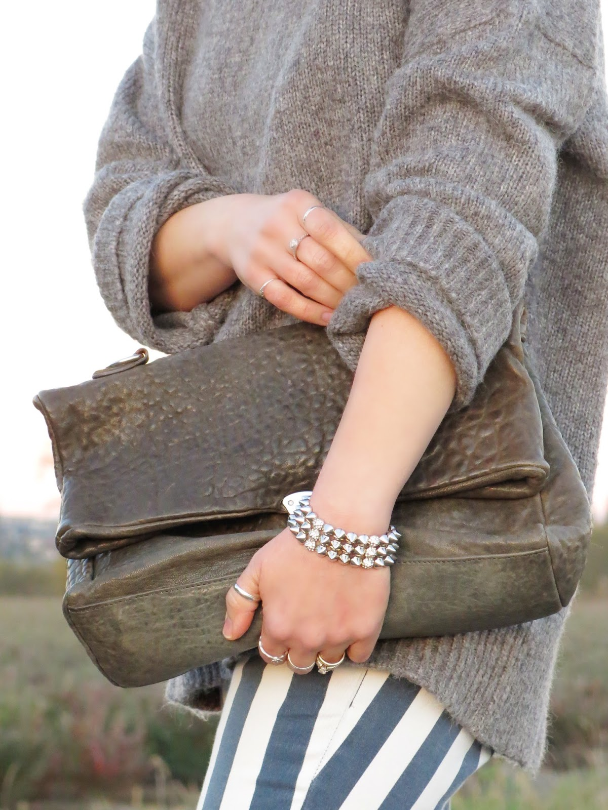 oversized turtleneck sweater, striped jeans, and accessories