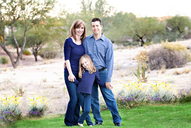 Sahuarita family stands in grass with desert landscape in background during photo shoot with local photographer