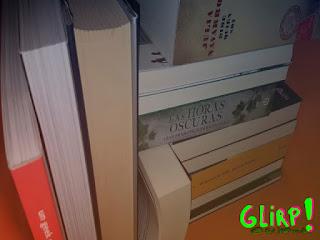 Libros de varios tamaños ordenados en una estantería. Unos de pie y otros en horizontal