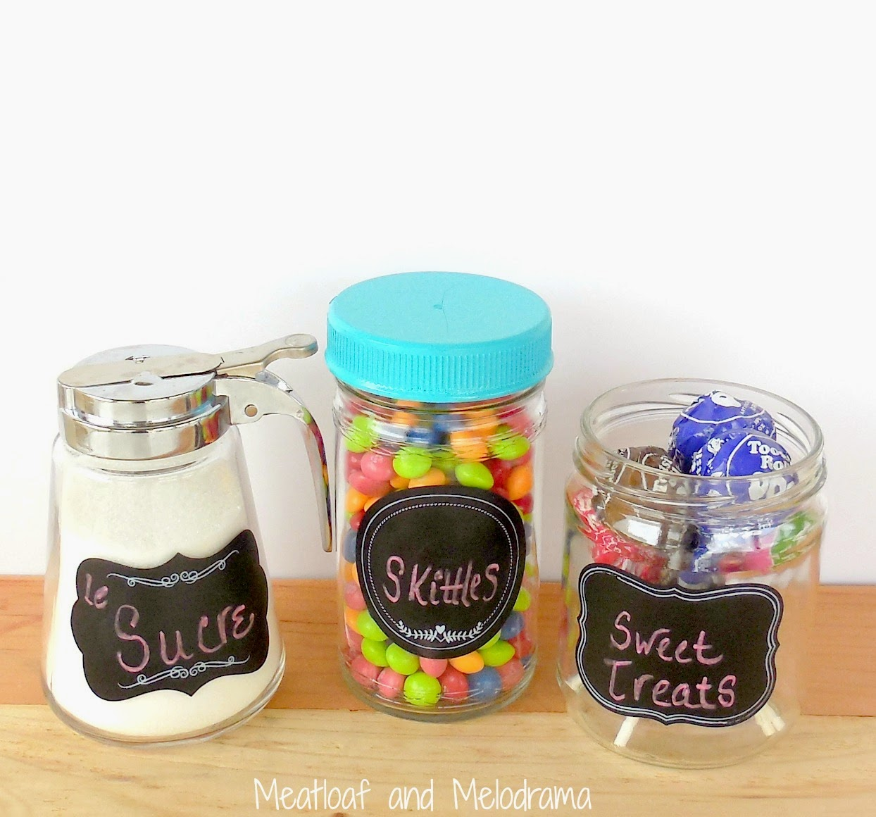 three glass containers with chalkboard labels and candy