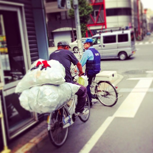 Homeless person and policeman on bicycles, Asakusabashi, Tokyo