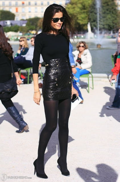 Woman wearing black shirt, high waisted black leather skirt and black leggings and heels.