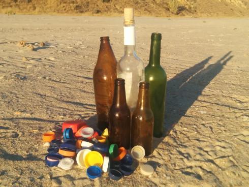 Botellas de cristal y tapones de plástico en la playa