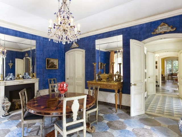 Traditional blue dining room in a NYC townhouse with painted floors, a crystal chandelier and antique round inlaid table
