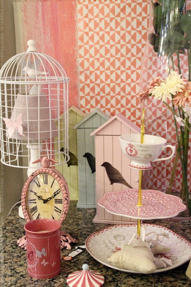 Wohnaccessoires in rosa und weiß im Interior Geschäft Domvs Artis in Palma Etagere Uhr Becher und Lampe vor gemusterter Tapete