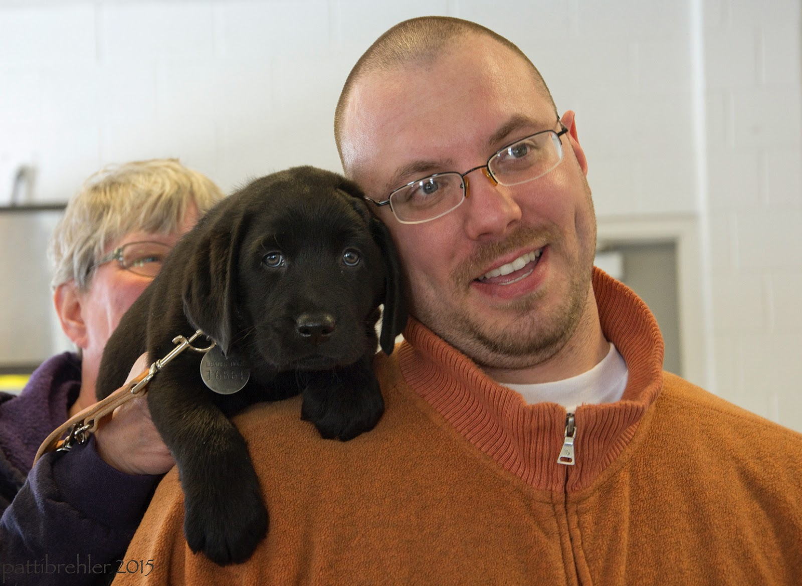The woman who was approaching is handing a small black lab puppy over the right shoulder of the man wearing an orange jacket. The man is leaning his head to his right against the puppy's head. The puppy's front paws are resting on the man's shoulder.