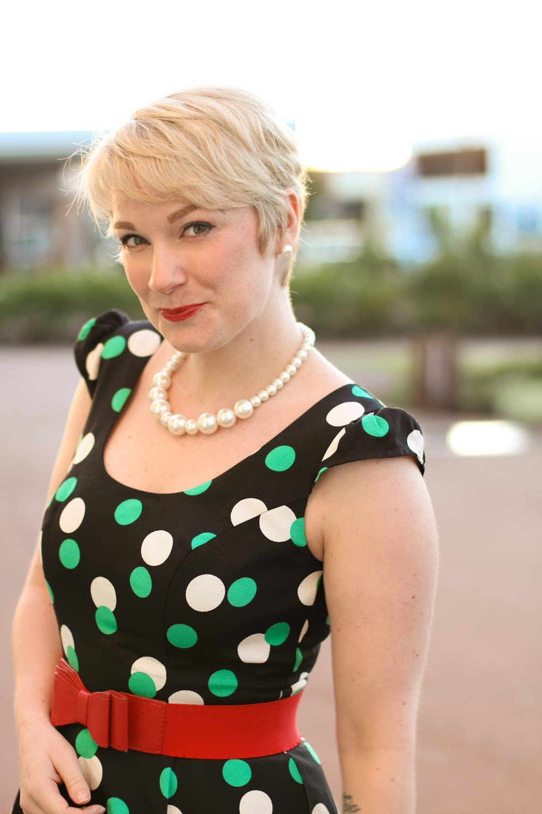 Liana of Finding Femme wears Review Australia polka dot dress with red Glassons belt and red patent pumps at Perth Oval.