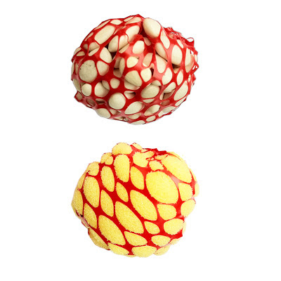 Two balls, one on top of the other. THe upper is constructed out of white beans wrapped in red netting, and the lower is a yellow sponge wrapped in red netting.