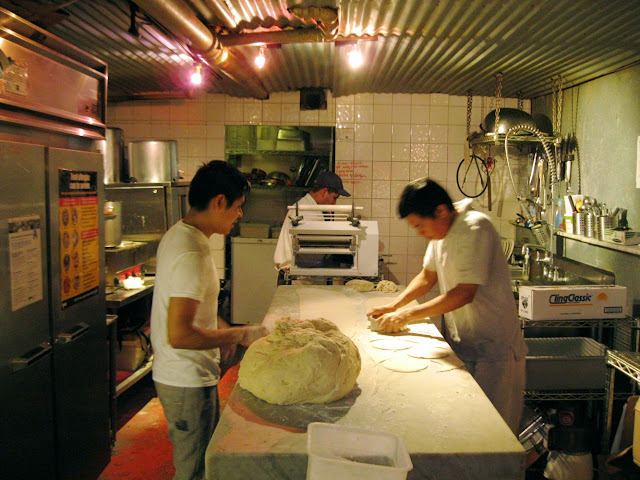 Cooks in the back stretch dough for meat pies at Tuck Shop in New York City