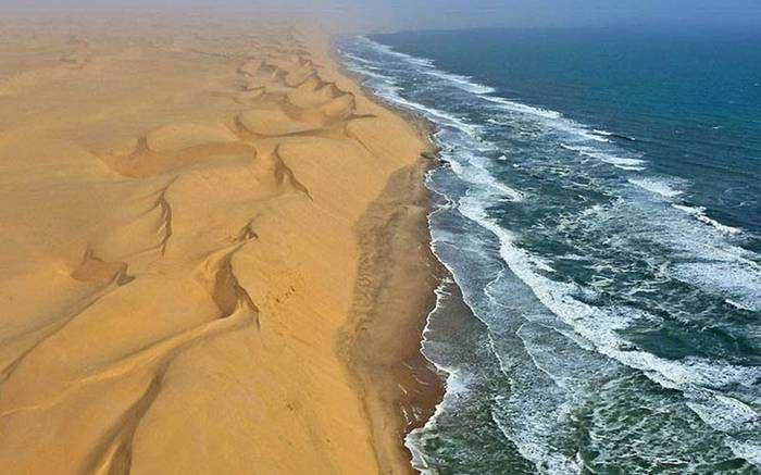 The Southern Namib desert is home to some of the tallest and most spectacular dunes of the world, ranging in color from pink to vivid orange. These dunes continue right to the edge of the Atlantic Ocean. The cold waters of the sea brushing against the dunes of the Namib desert is one of the most surreal sights.