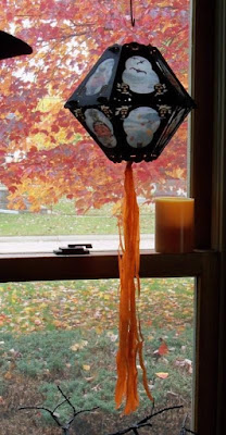 12-sided lantern with pumpkins and blue panes contrasts beautifully with the yellows, oranges, and reds of the autumn landscape from the window view.