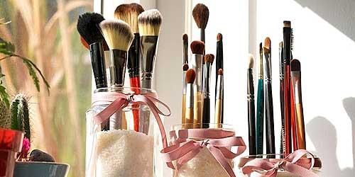 brochas de maquillaje en vasos de cristal