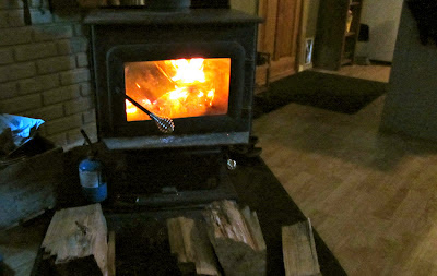 roaring fire in our wood stove with extra wood stacked in front of it