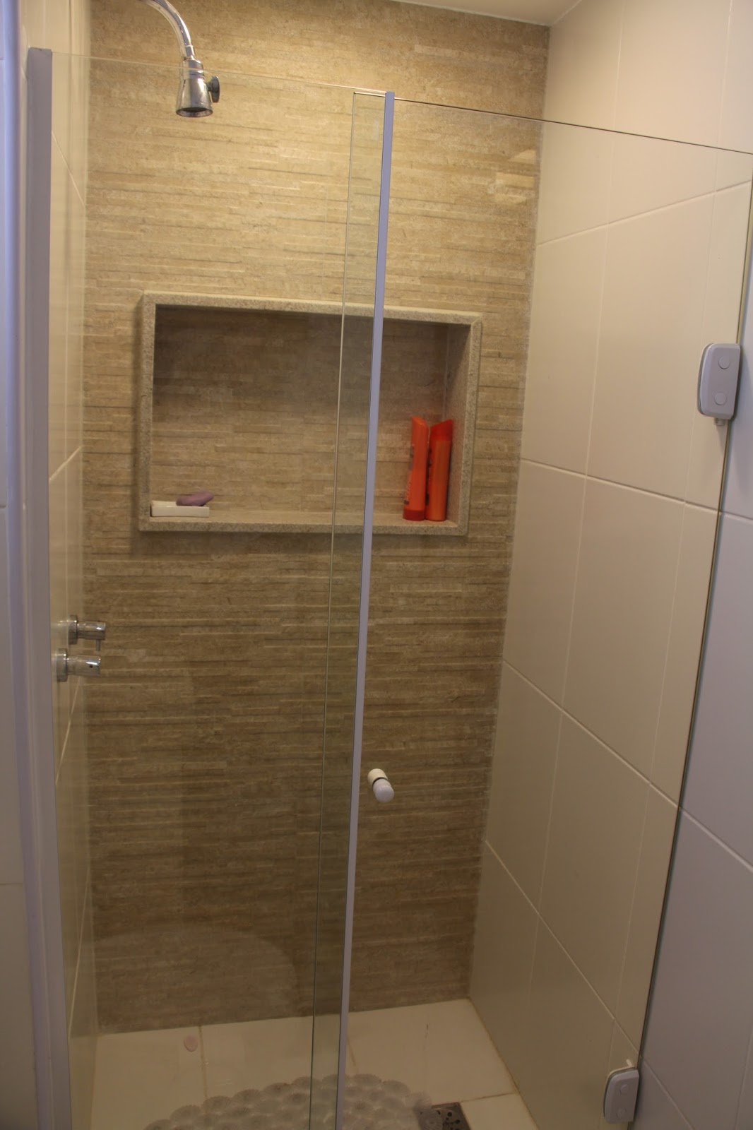 No banheiro da suíte o box recebeu revestimento decorativo e nicho  #AF3D1C 1066 1600