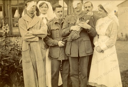 Photograph of wounded officers, with a cat, standing with two nurses outside an unidentified military hospital, c.1916 - 1918 (D/DLI 7/951/9(30))