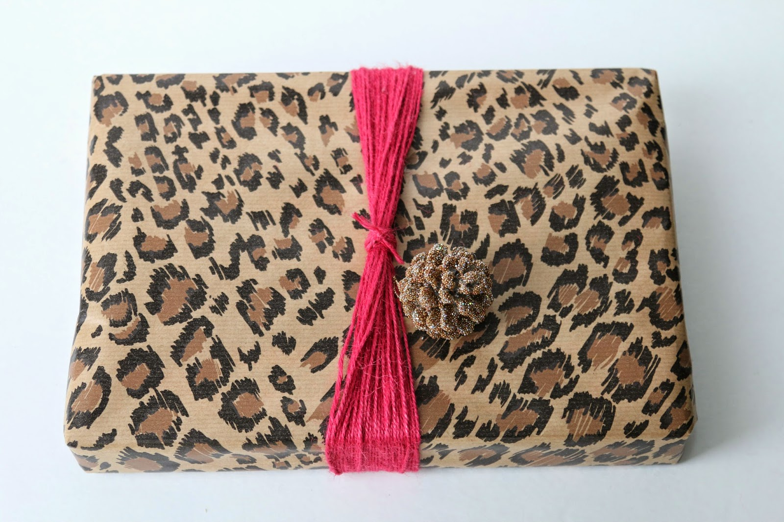 Holiday gift wrapping with animal print paper and raspberry yarn