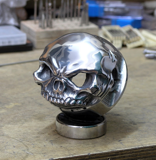 Triumph over adversity skull piston carving