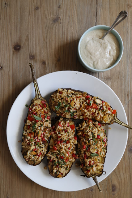 A plate of aubergines stuffed with oats, on a wooden background