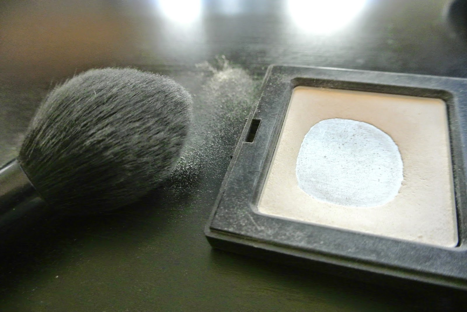 Setting powder on brush, compact shown with obvious wear.