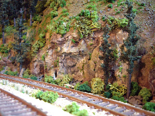 Scenic details of rock face, ballast, and vegetation along tracks