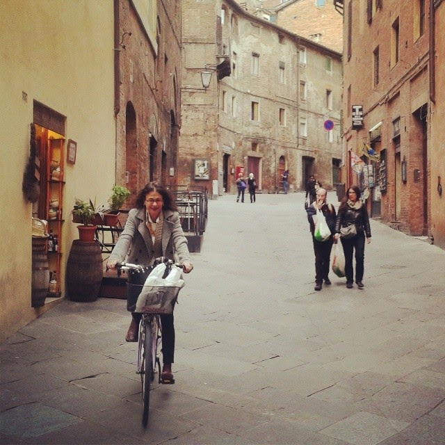 Nina arriving on her bike for lunch in Siena's town center