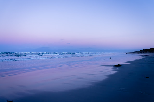 pink and mauve coloured sunrise over beach