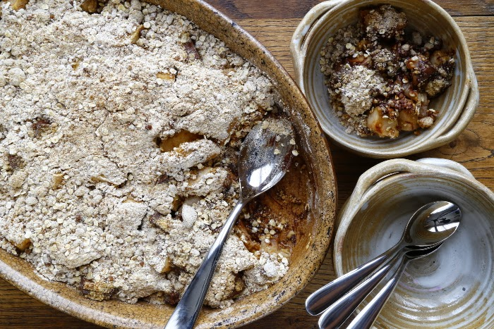 A dish of pear and chocolate crumble and serving bowls