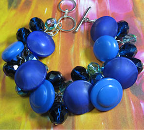 Glamorous chunky bracelet has clusters of shiny blue beads and buttons