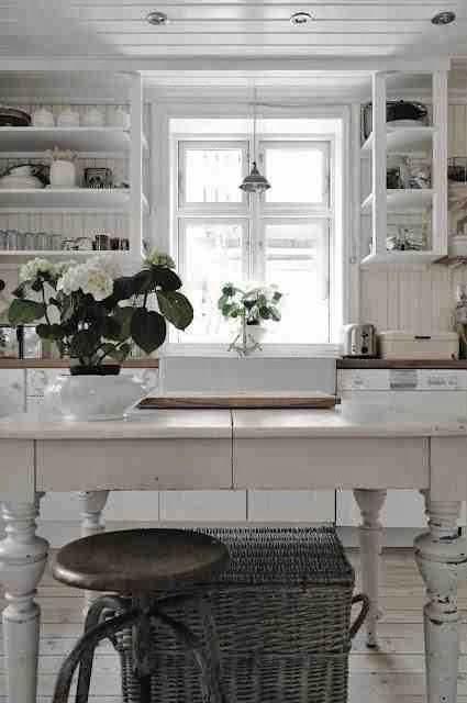 Rustykalna kuchnia, białe meble kuchenne, otwarte półki na naczynia, drewniany stół na tłoczonych nogach, stół vintage, metalowy taboret