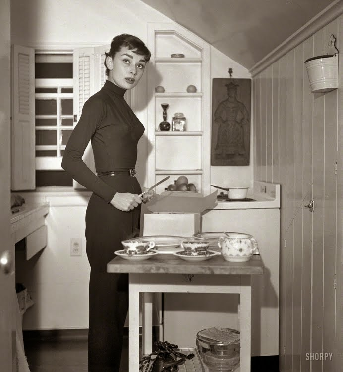 Circa 1953, Actress Audrey Hepburn at home preparing and serving coffee and cake.