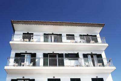 Une maison blanche avec des garde-corps tout le long de ses terrasses.