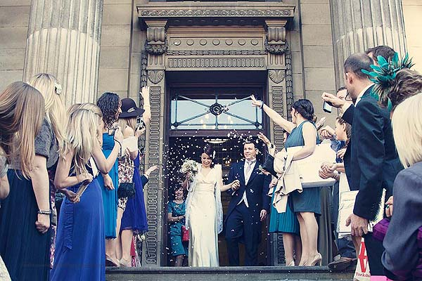 guests throwing confetti at the bride and the groom at Marylebone Town hall wedding