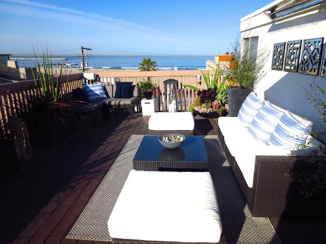 rooftop ocean view roof deck outdoor living room woven furniture plants beach