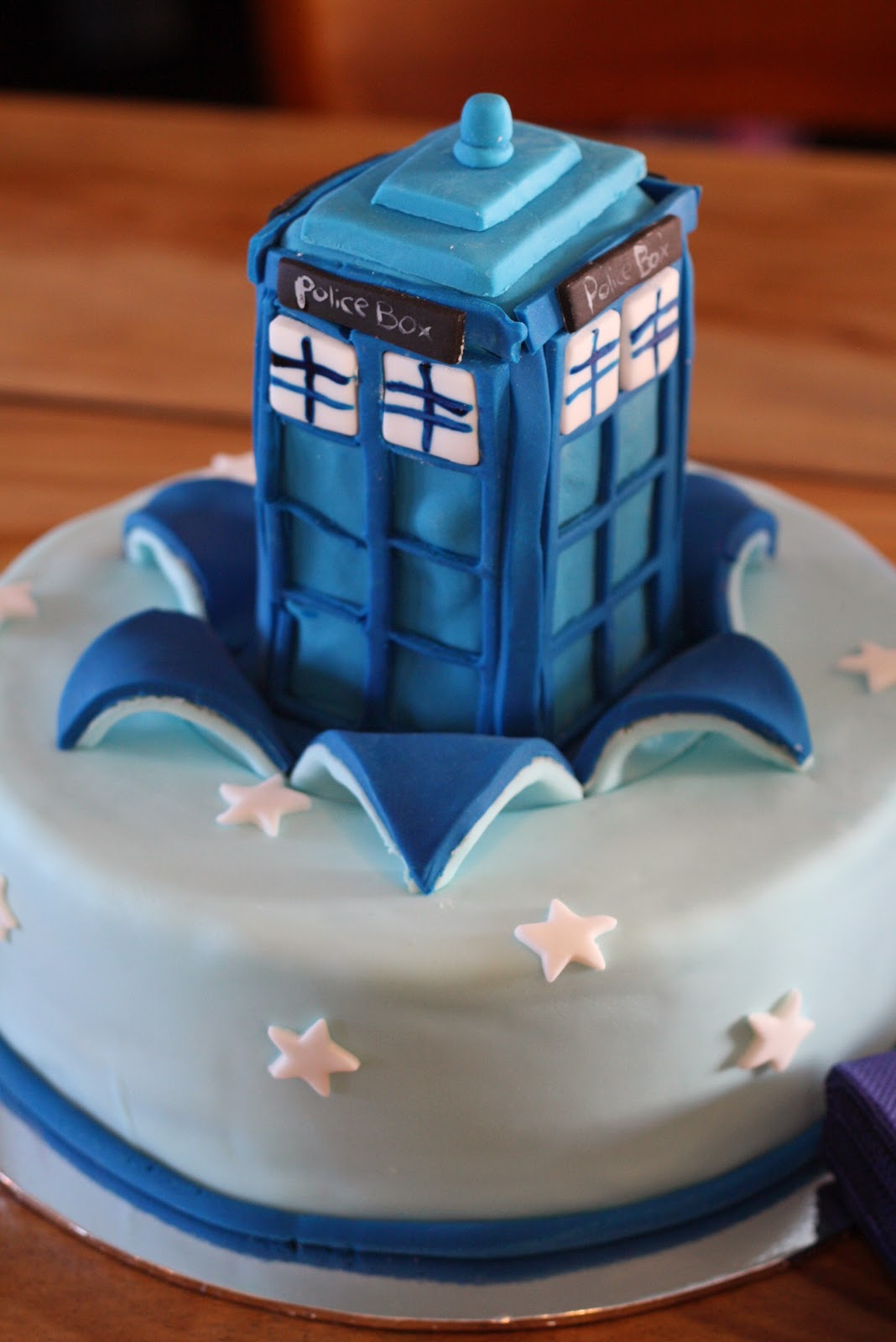 A blue cake with a fondant-ed tardis sitting on top.