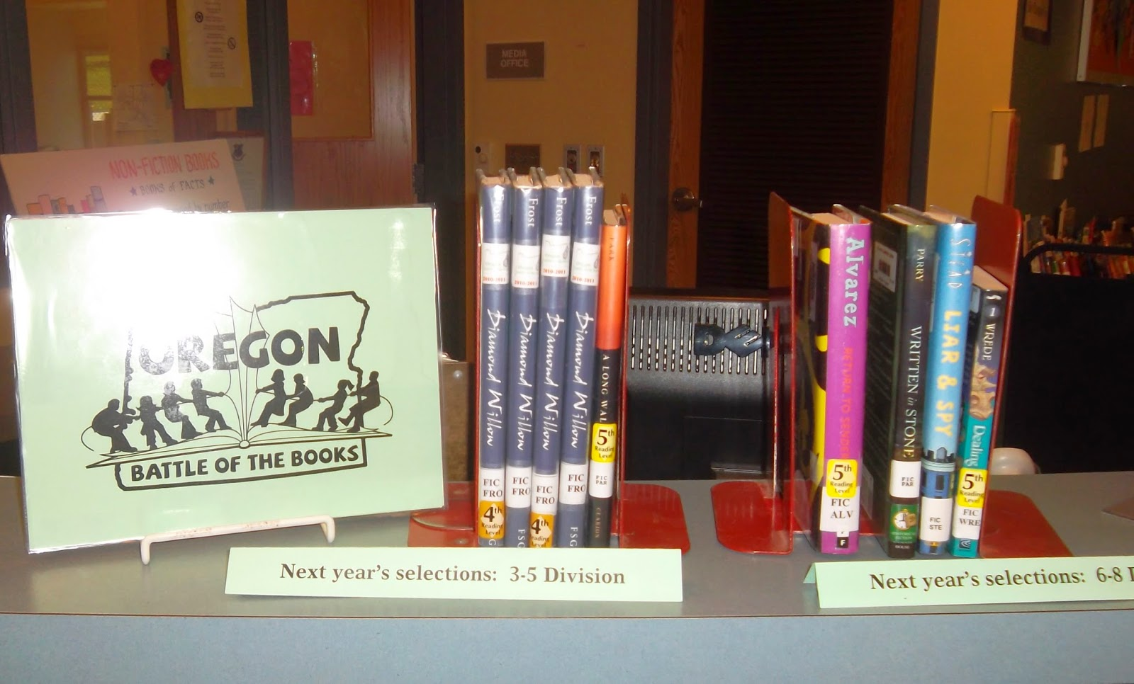 Two sets of books shelved between bookends, their spines facing outward. Tented signs in front of them designate the third-to-fifth grade divisions and sixth-to-eighth grade divisions, Oregon Battle of the Books. To the left, a green sign with the logo for Oregon Battle of the Books logo is propped in a wire stand.