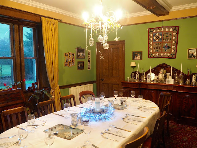 The dining room for Christmas dinner, with silver bauble, fairy lights, candles, and natural leaf and stick wreaths
