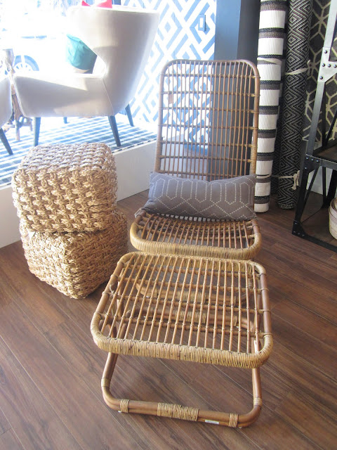 rattan lounge chair next too two wicker cubes stacked on top of each other