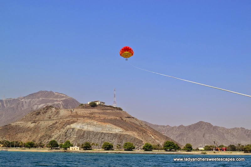parasailing with a fantastic view of the Hajar Mountains