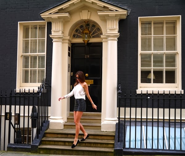 Cream cashmere jumper and black leather skirt against a Mayfair townhouse