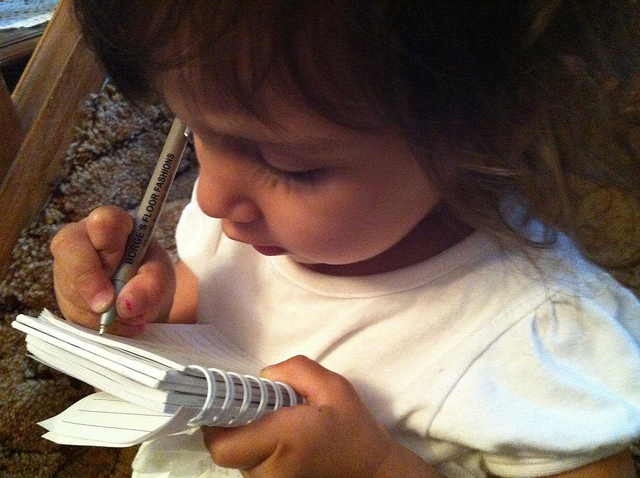 A little girl writing on a pad