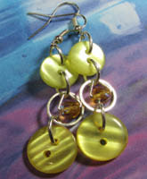 Pretty long strand earrings have small beads encircled in silver rings as a focal point between 2 yellow buttons