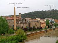 Vista de l'església de Santa Maria, la Xemeneia de Les Culleres i les muralles de la Riereta des del Pont Vell