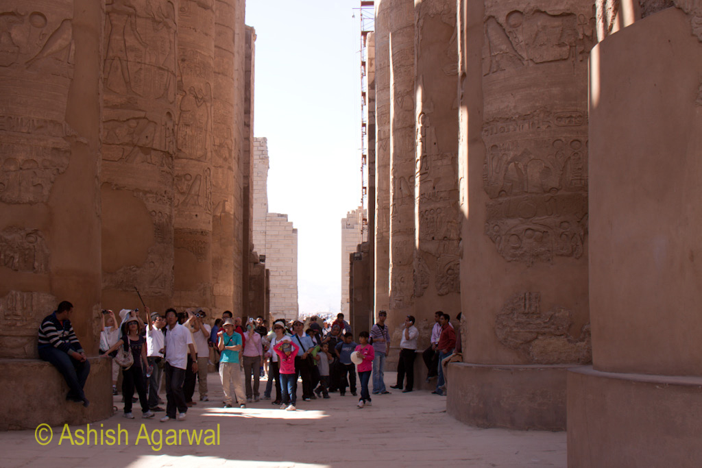 Tourists at the base of the pillars of the Hypostyle Hall in the Karnak temple in Luxor