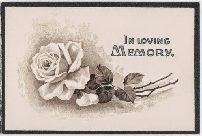 "Black bordered off white card, image of a white rose and words ""In Loving Memory"""