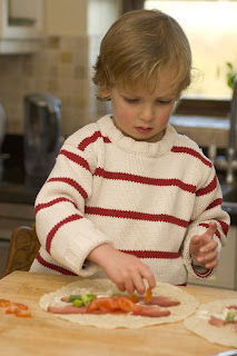 young boy making wraps for after-school snack