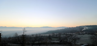 Mist in the valley, and the morning fire in a villager's house