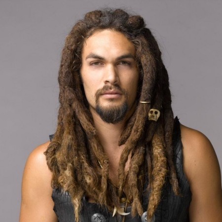 Jason Momoa posing for a picture with his natural hair in dreadlocks.