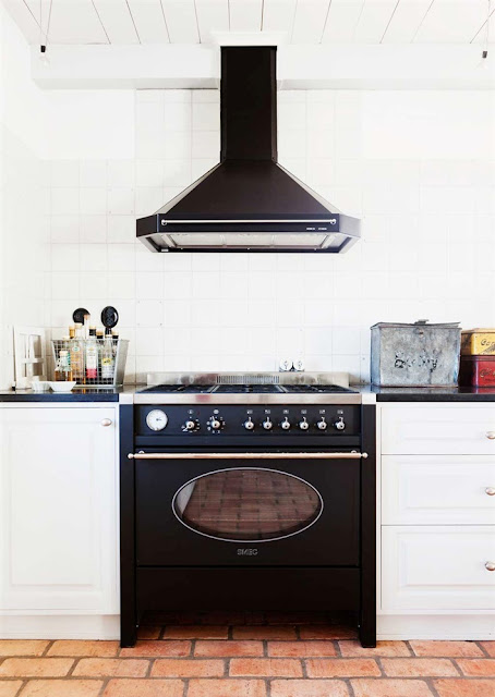 gas range in the kitchen in black with a white tile backsplash